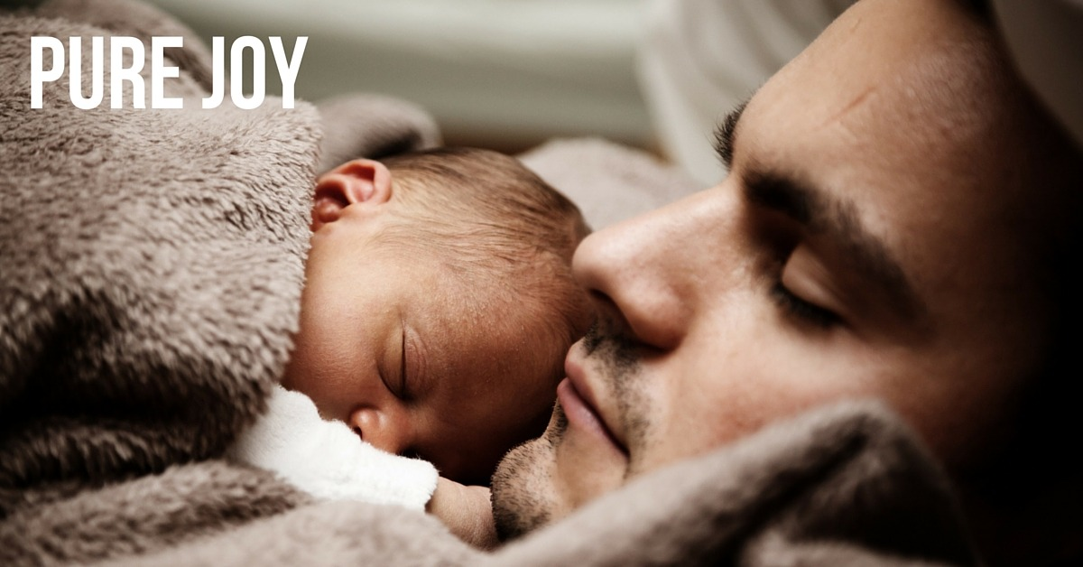 Image of a baby sleeping on a father with text 'Pure Joy'