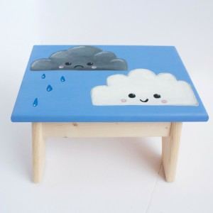 Image of a step stool with two clouds painted on it.
