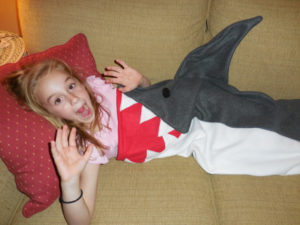 Image of a girl wrapped in a blanket that looks like a shark