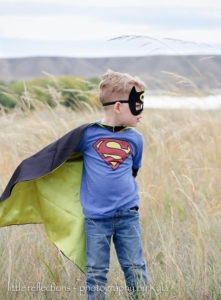 Image of a boy wearing a cape and mask from LCAApparel and Gifts